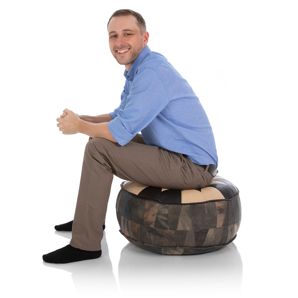 Junger Mann sitzt auf einem orientalischen Pouf Ottoman aus Ziegen-Leder