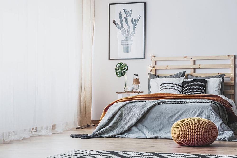Ein gelbes Pouf-Kissen steht in einem hellen Schlafzimmer vor dem Bett als Sitzhilfe