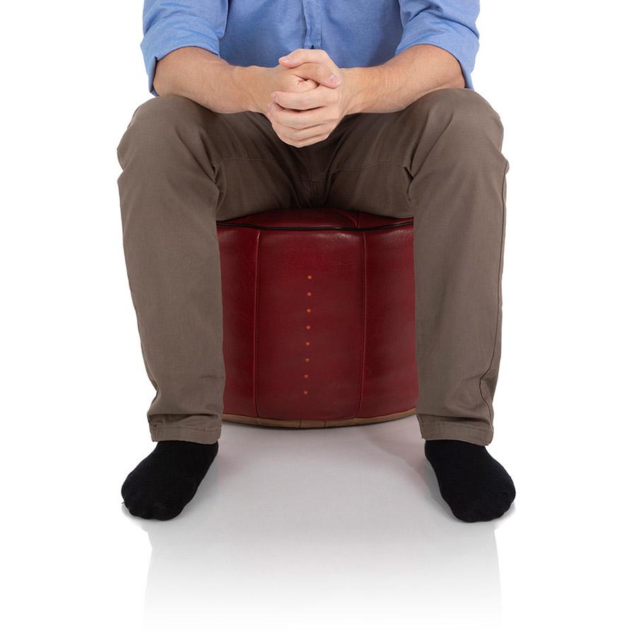 Fest gefüllter Pouf mit gestanzten Löchern, auf dem ein junger Mann sitzt
