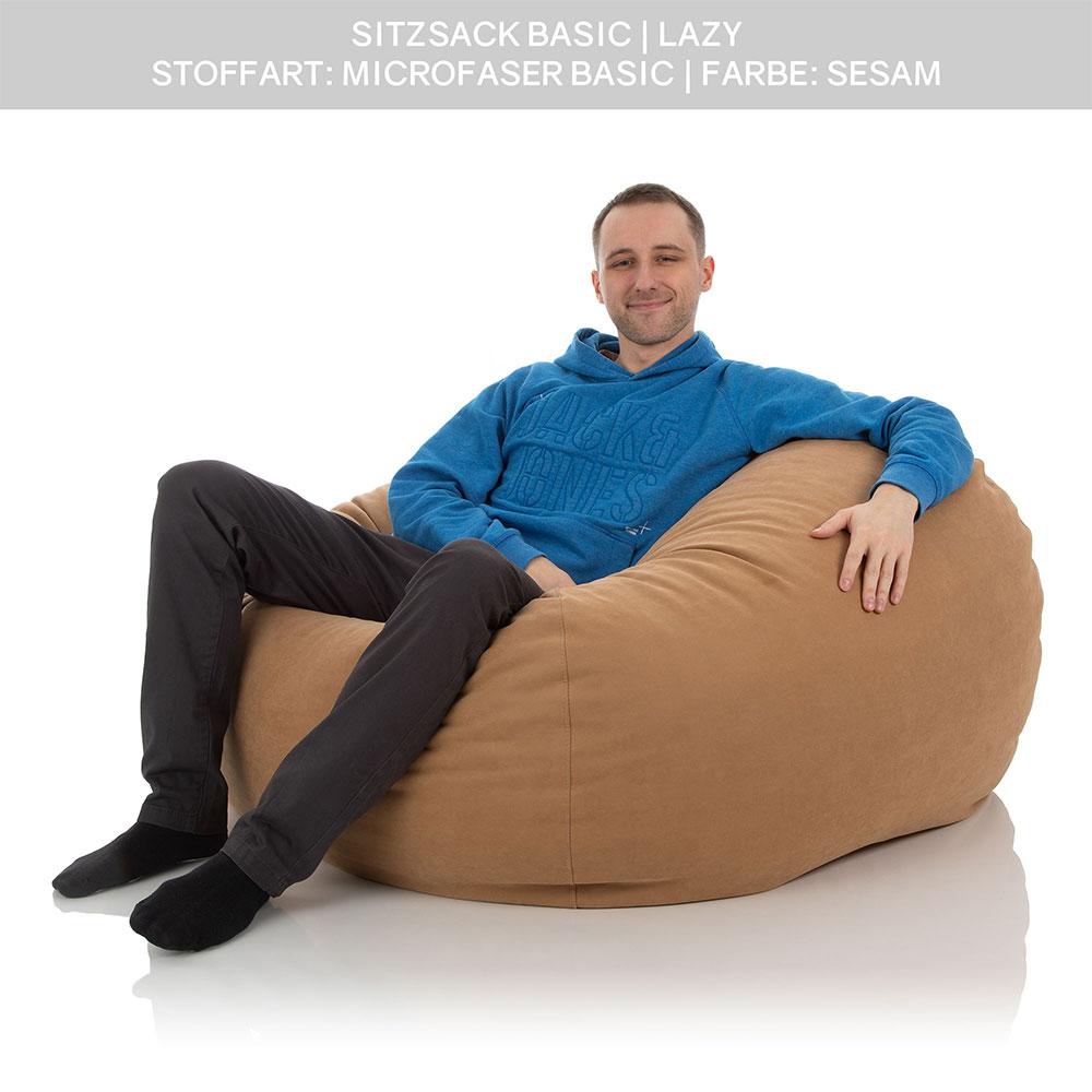 Ein junger Mann versinkt bequem in einen XXL Sitzsack Lazy der Farbe Sesam