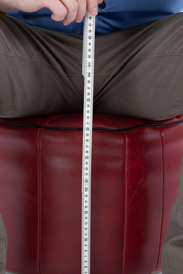 Mit einem Zollstock wird die Höhe eines Pouf Ottoman bei Belastung gemessen