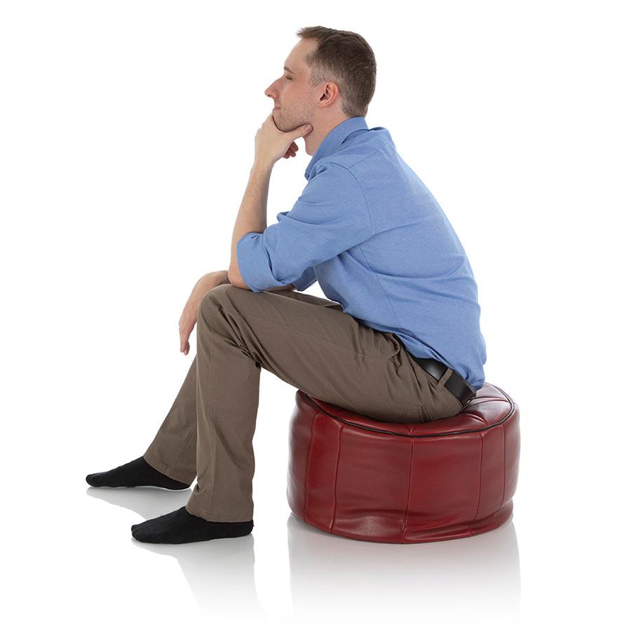 Junger Mann sitzt auf einem orientalischen XXL Pouf aus rotem Kunstleder