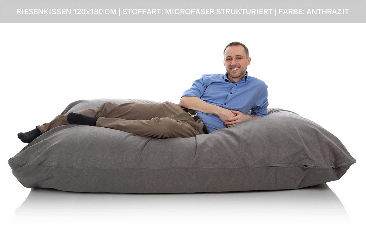 Ein junger Mann liegt gestreckt auf einem XXL Sitzsack Liegesack 120x180 cm anthrazit