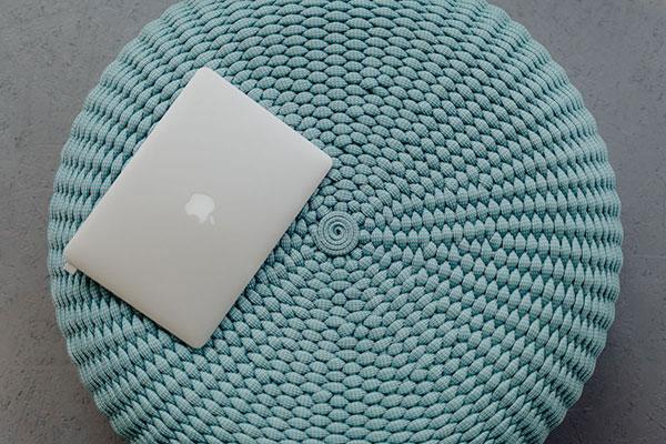 Ein Apple Laptop liegt auf einem blauen Pouf mit Innenhülle aus Strickwolle