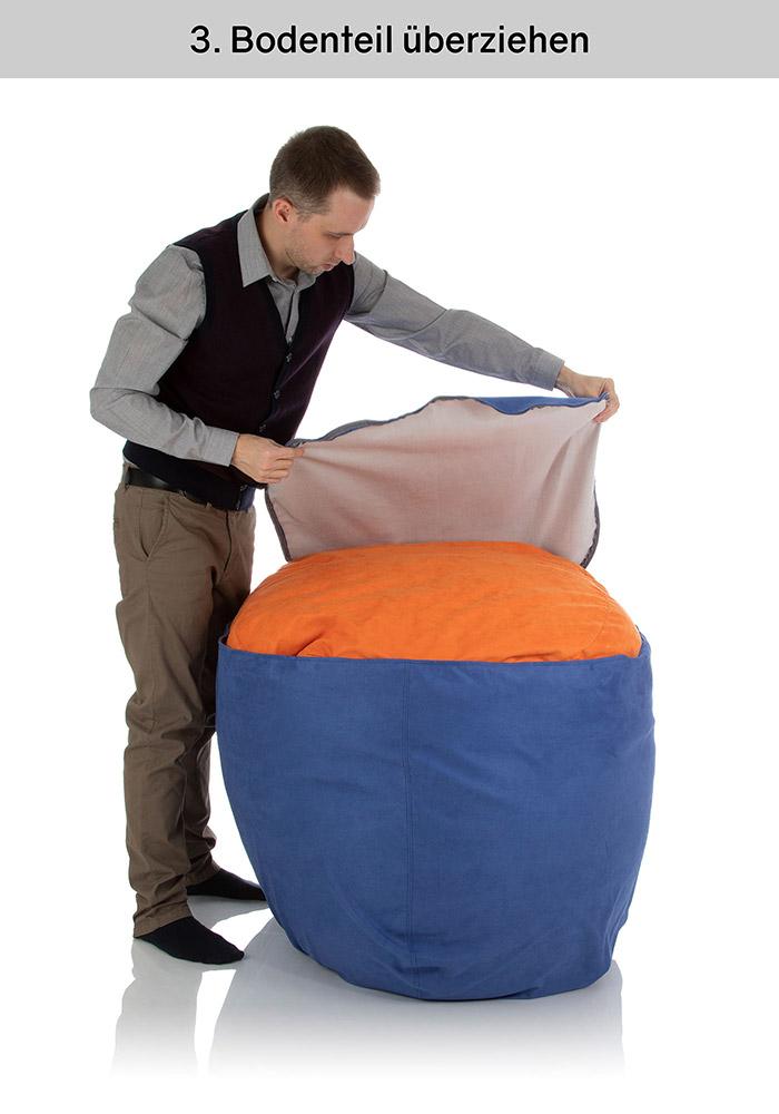 Junger Mann stellt den Sitzsack auf den Kopf und zieht das Bodenteil mit Reißverschluss über die Innenhülle