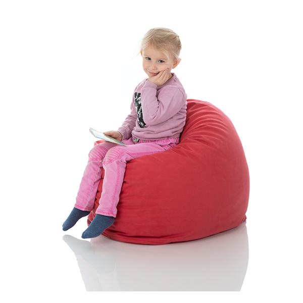 Ein kleines Maedchen sitzt komfortabel in einem roten Sitzsack fuer Kinder