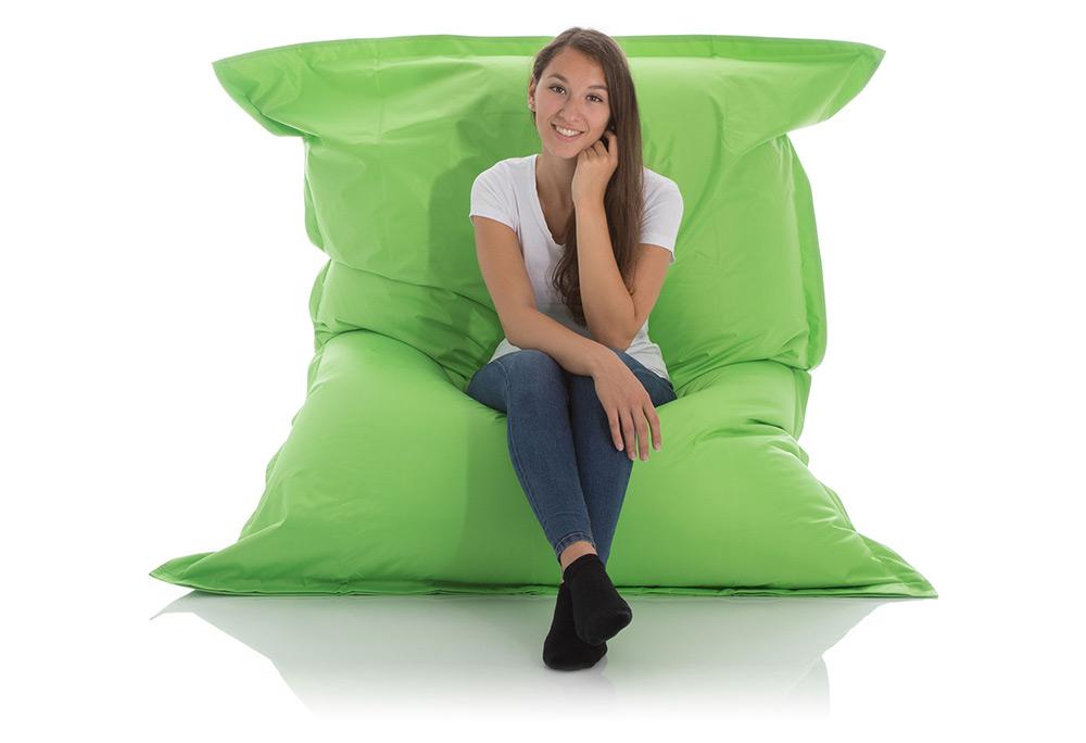 Junge Frau sitzt im aufrechten XXL Outdoor Sitzsack Fashion in grün