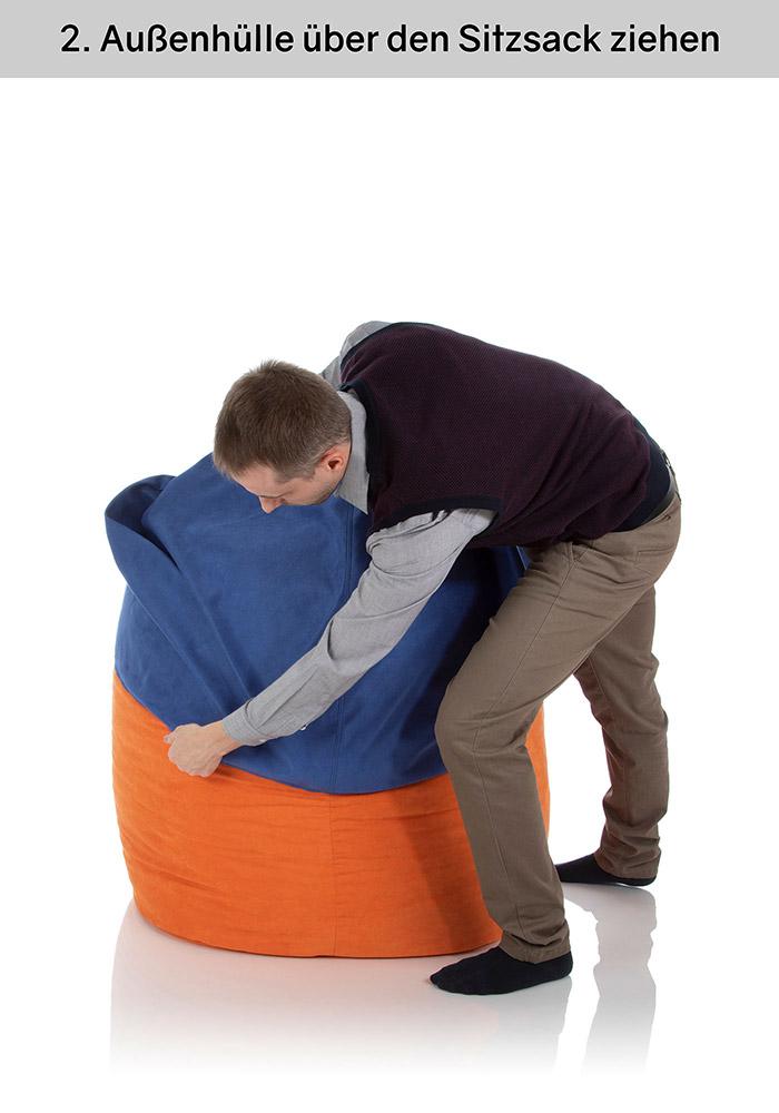 Junger Mann zieht eine Außenhülle über die gefüllte Innenhülle eines Sitzsacks