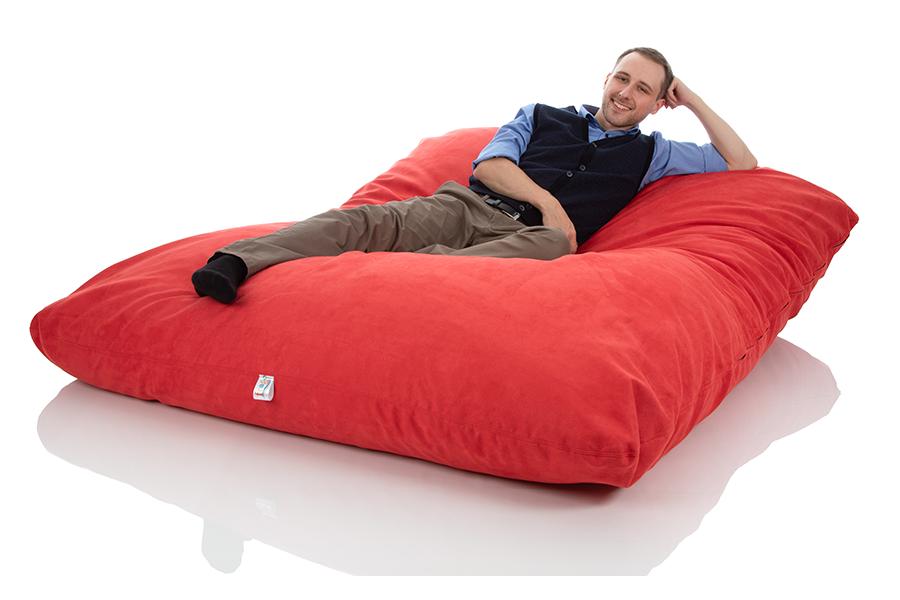 Junger Mann liegt in einem riesigen XXL-Sitzsack Bodenkissen rot der Groeße 140x180 cm