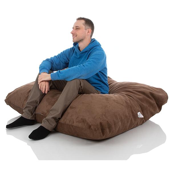 Junger Mann sitzt gemuetlich auf einem grossen Kissen braun 100 x 120 cm