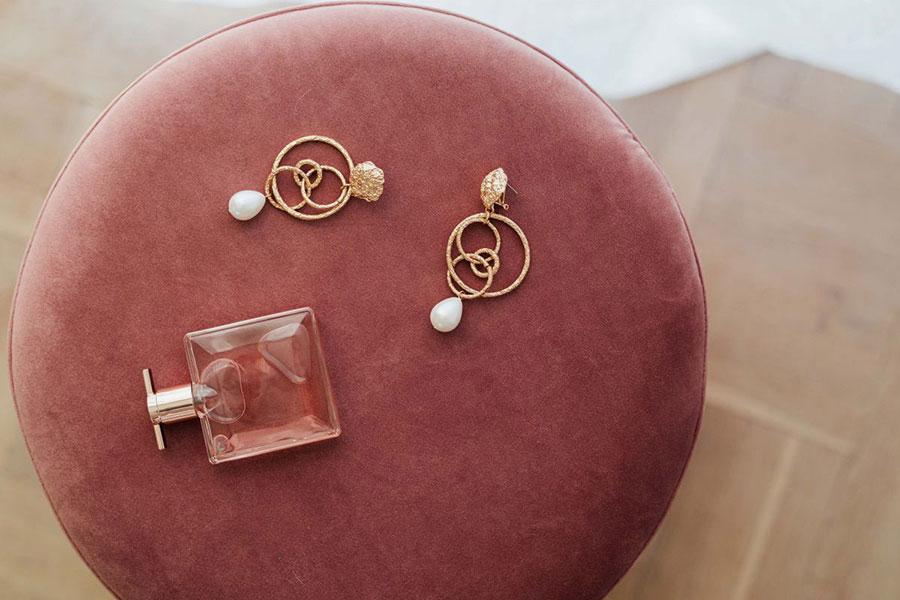 Ein roter Pouf Ottomane aus Microfaser wird als Ablage für Ohrringe verwendet