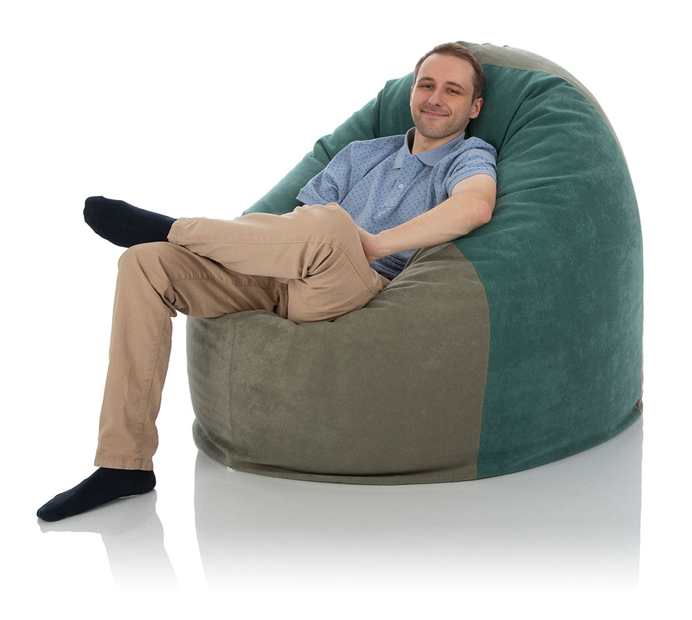 Junger Mann versinkt in riesigem, mehrfarbigen XXL Sitzsack mit übergeschlagenem Bein