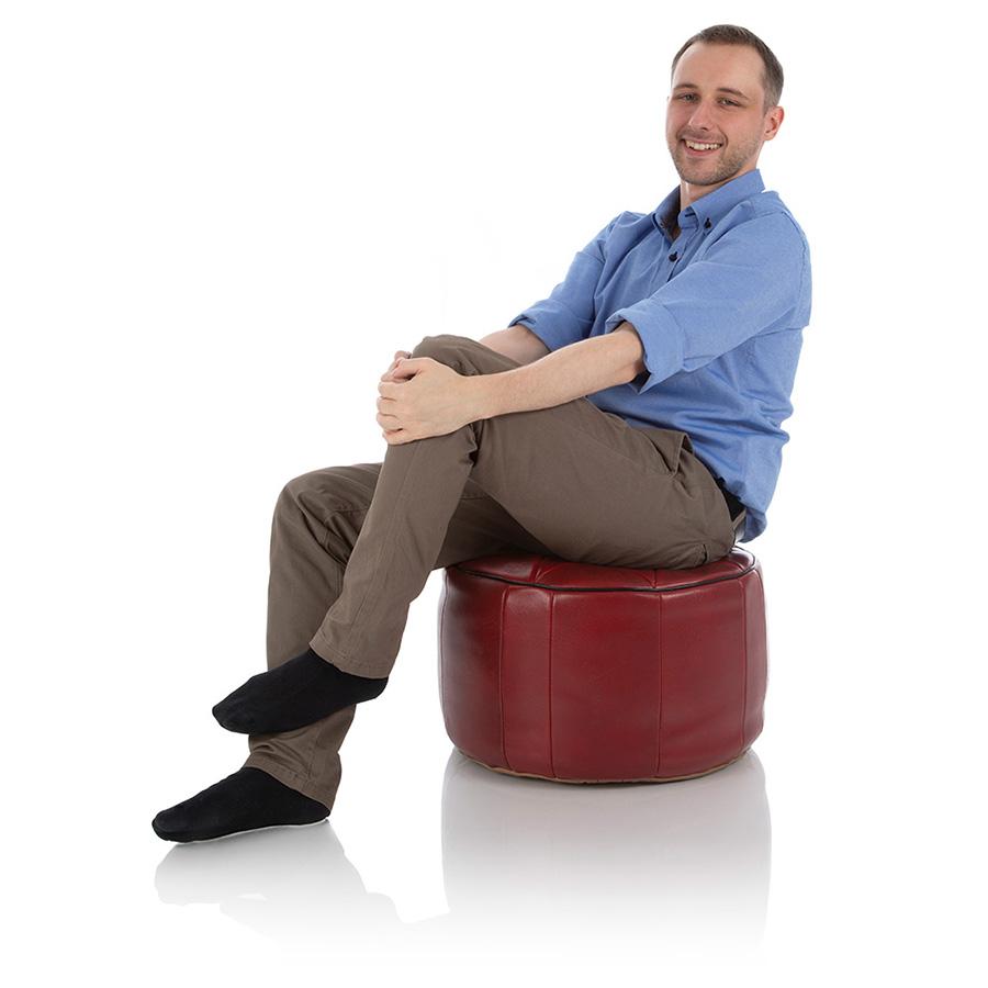 Junger Mann sitzt auf einem großen roten Pouf Ottoman aus Marokko