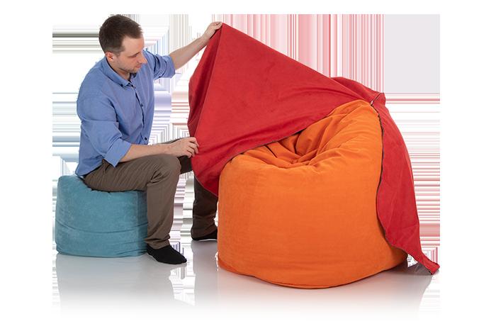 Junger Mann zieht einen roten Sitzsack-Bezug über einen Sitzsack orange