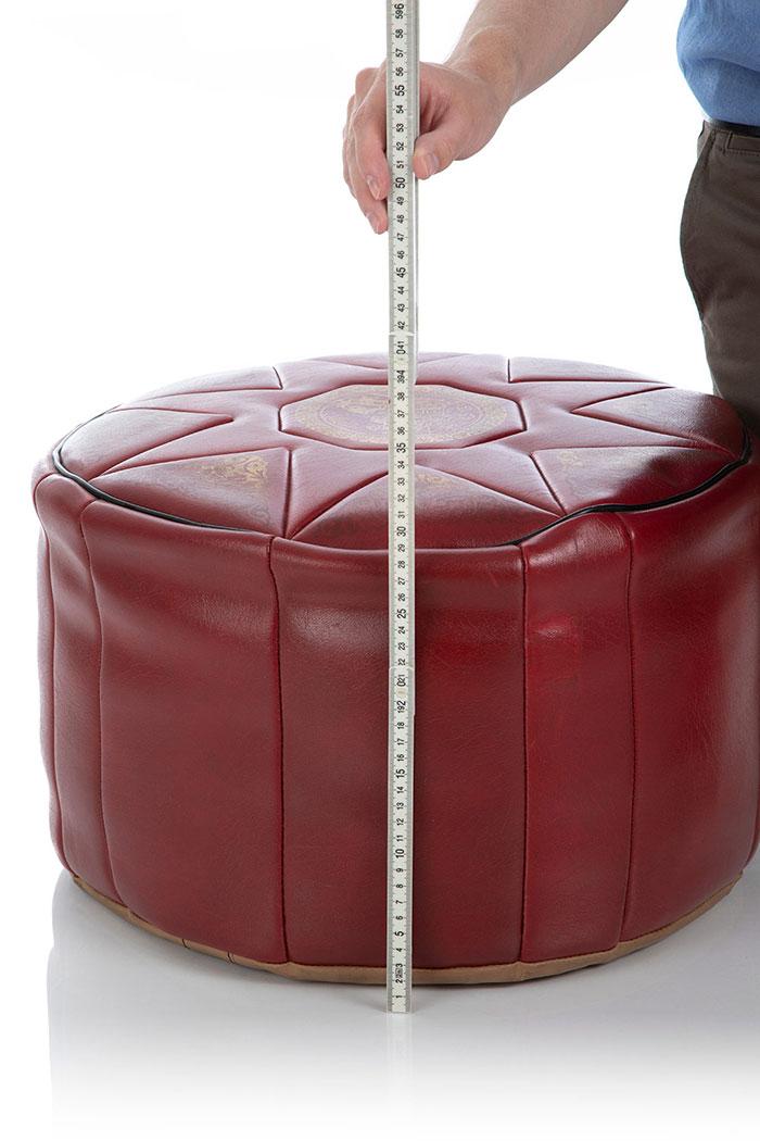 Mit einem Zollstock wird die Höhe eines XXL Pouf Hockers gemessen