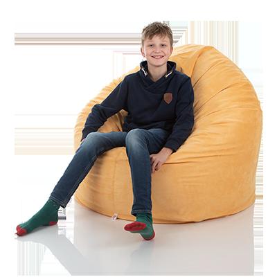 Ein Jugendlicher sitzt in einem bequemen XXL Sitzsack für Kinder gelb