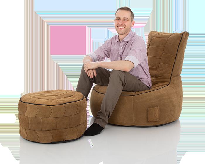 Junger Mann sitzt in einem XXL Lounge Sitzsack aus braunem Wildleder mit Pouf