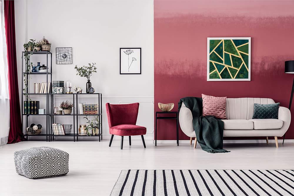 Ein rechteckiger Pouf mit schwarz-weißem Muster in einem modernen, rot-weißem Wohnzimmer