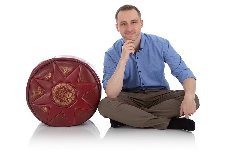 Junger Mann sitzt neben einem großen Kunstleder-Pouf mit goldenem Aufdruck