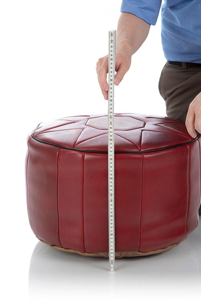 Mit einem Zollstock wird die Höhe eines prall gefüllten XXL Pouf Sitzkissens gemessen