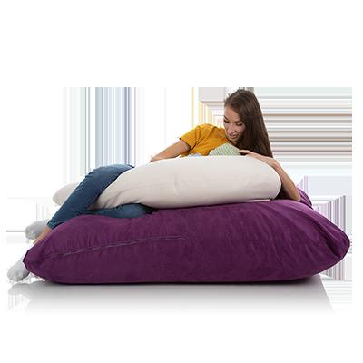Junge Frau liegt auf einem XXL Bodenkissen violett mit einem weissen Stillkissen