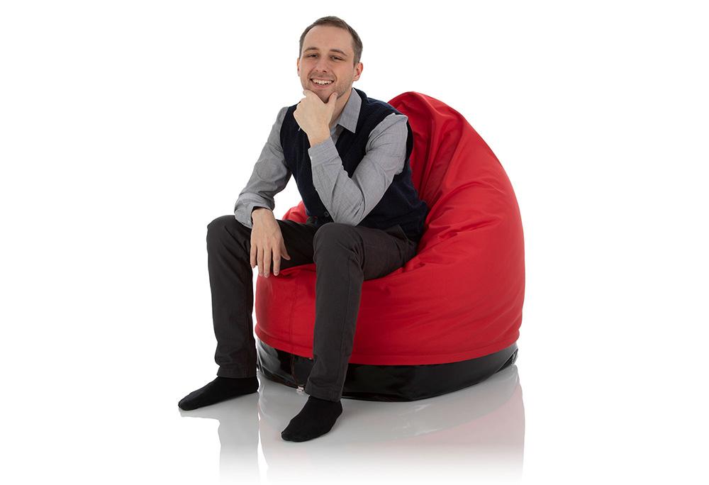 Junger Mann sitzt im Outdoor Sitzsack Sunny rot für Kinder und Jugendliche aus Cordura Nylon