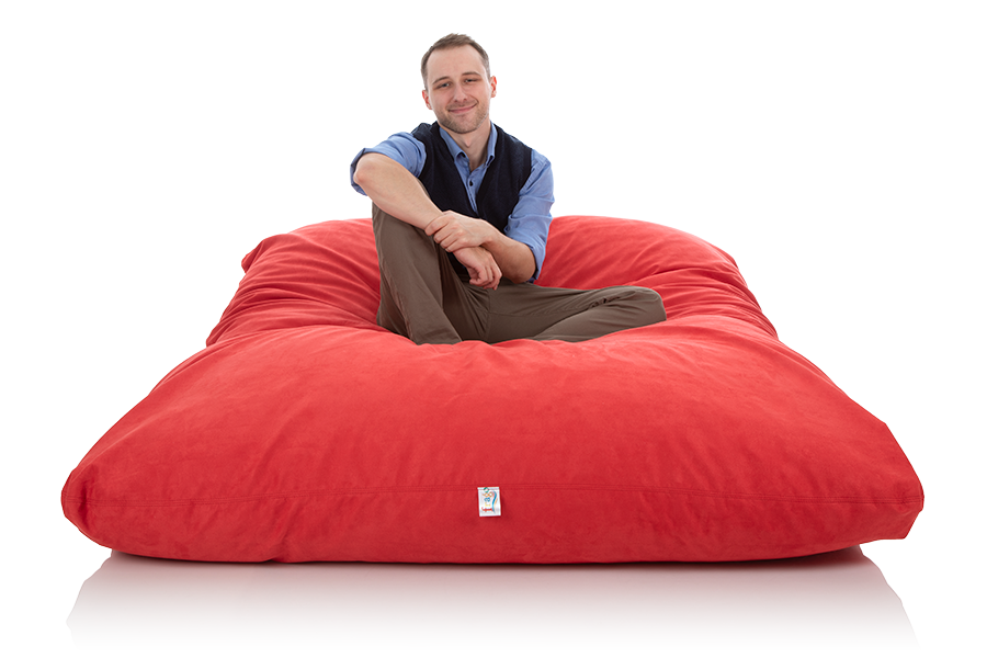 Junger Mann sitzt aufrecht auf einem riesigen XXL Sitzsack rot der Groeße 140 x 180 cm