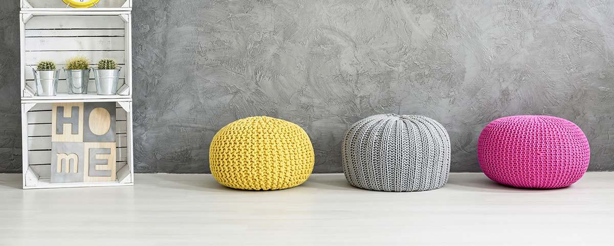 Drei bunte Pouf-Hocker aus grober Strickwolle vor grauem Hintergrund