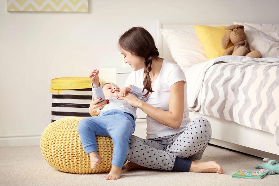 Eine junge Mutter spielt mit ihrem Kind auf einem gelben Pouf aus Wolle