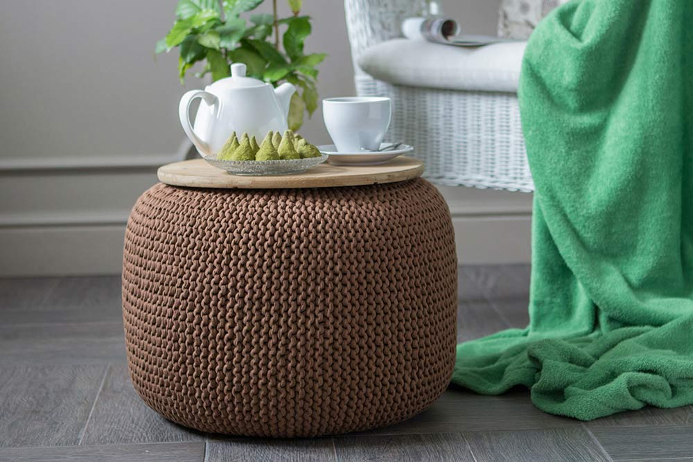 Ein brauner Pouf-Hocker aus Wolle wird als Ablagefläche für ein Tee-Set verwendet