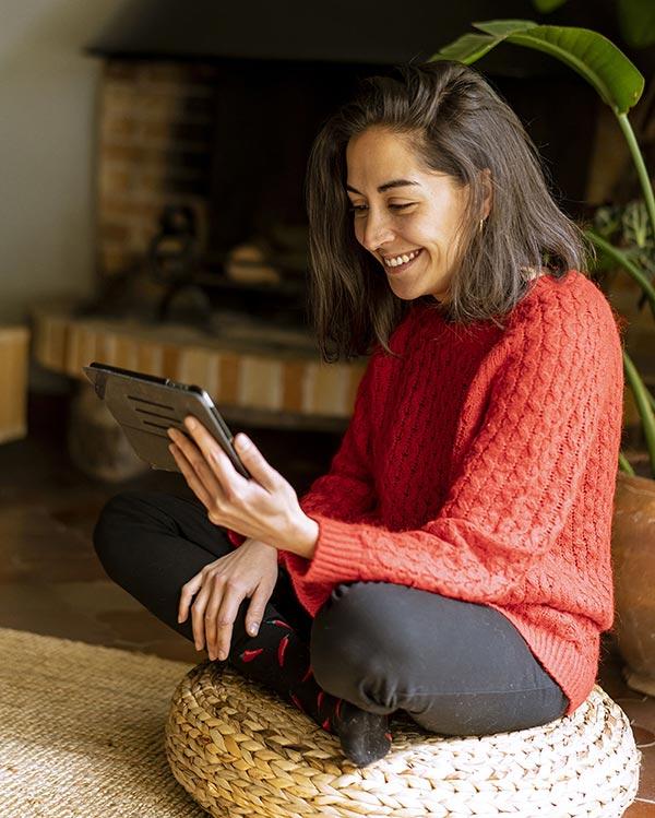 Eine junge Frau in rotem Pullover sitzt auf einem Pouf-Kissen aus Jute und liest