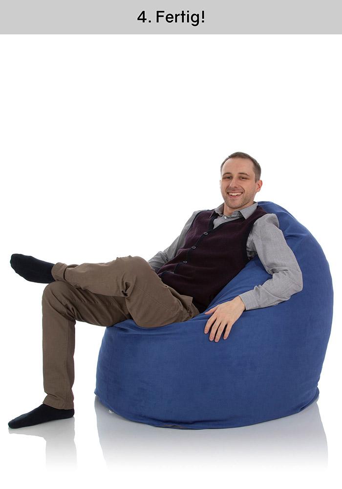 Junger Mann sitzt bequem in einem großen, mit einer Außenhülle überzogenen Sitzsack