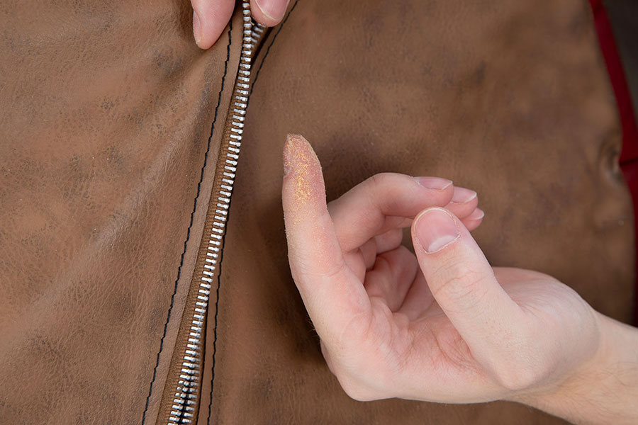 Staub der Holzwolle-Füllung aus dem Inneren eines Poufs am Finger