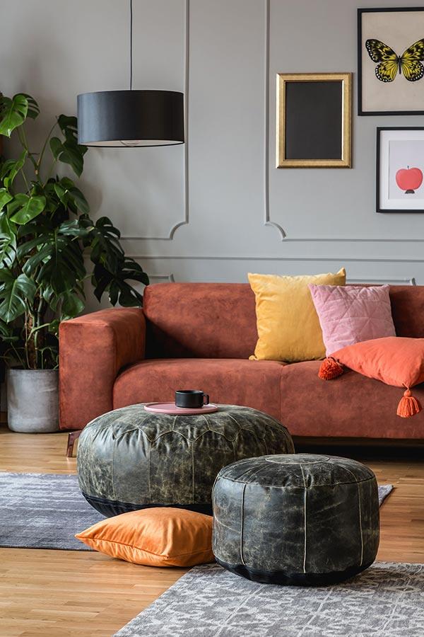 Zwei Leder Poufs verschiedener Größen stehen in einem Wohnzimmer vor einem Sofa
