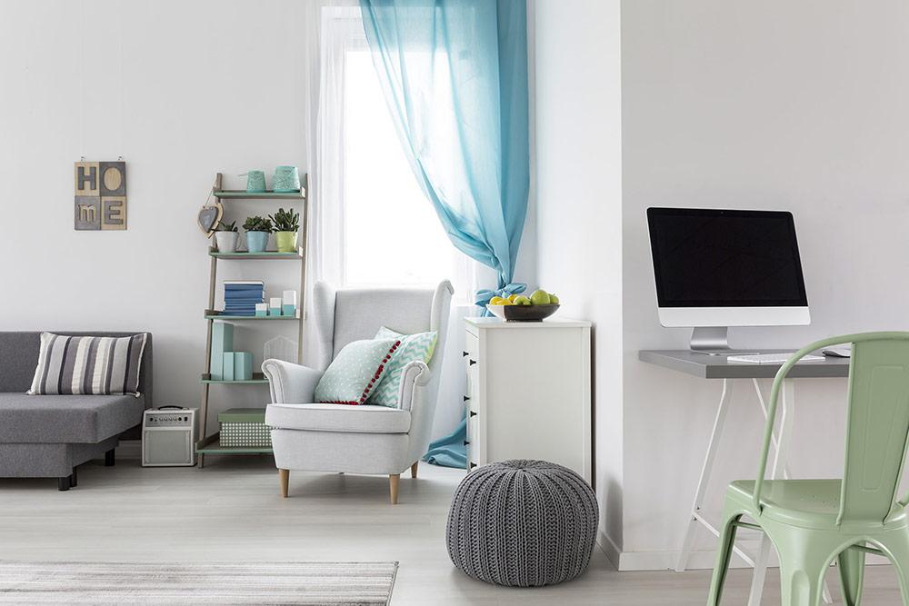 Ein grauer Pouf steht in einem Zimmer neben anderen weißen und grauen Möbeln