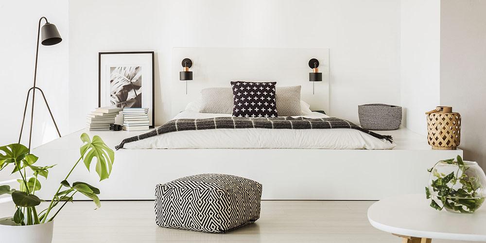 Ein rechteckiges Pouf-Bodenkissen mit schwarz-weißem Muster in einem Schlafzimmer