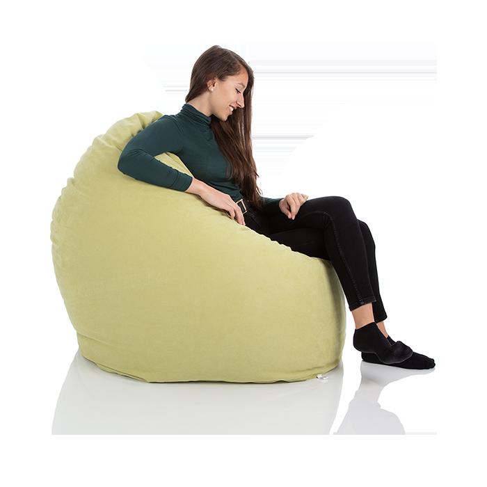 Junge Frau sitzt in einem gruenen XXL-Sitzsack Relax von Sitjoy