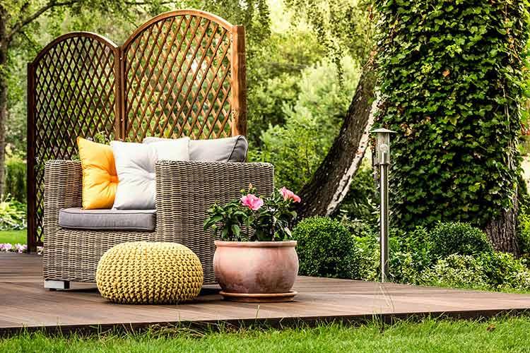Ein gelber Strick-Pouf in einem grünen Garten auf einer Holz-Terrasse
